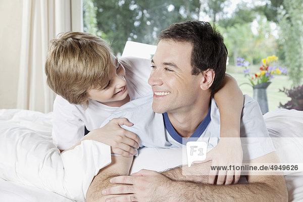 Mit seinem Sohn auf dem Bett lächelnd mann Mit seinem Sohn auf dem Bett lächelnd mann