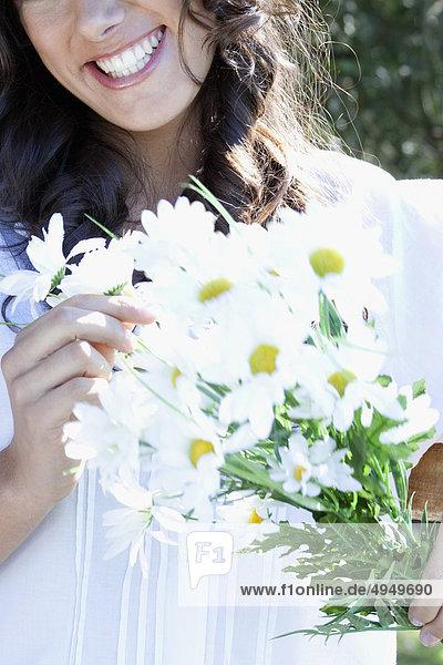 Frau hält Blumen und lächelnd