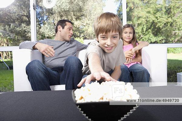 hinter sitzend Junge - Person Menschlicher Vater Schwester Popcorn aufheben