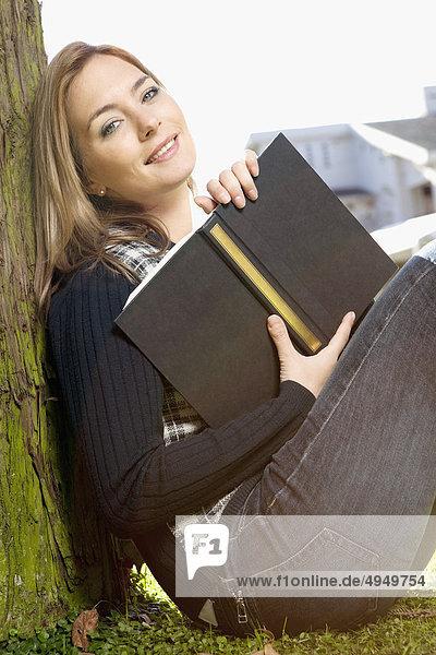 Frau sitzen im Park und  ein Buch hält