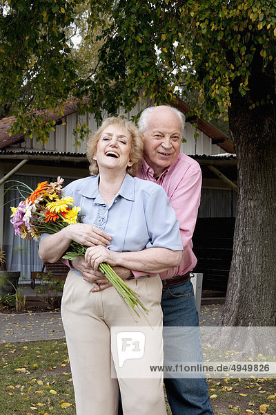 Woman holding a bouquet of flowers with her husband hugging her