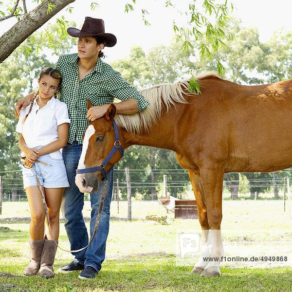 Paar Standing mit einem Pferd in einer farm