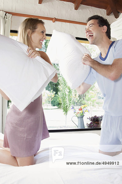 Couple having a pillow fight in a bedroom