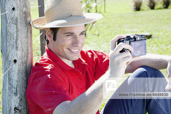 Mann Aufnahme eines Bildes mit einer digitalen Kamera in einem park