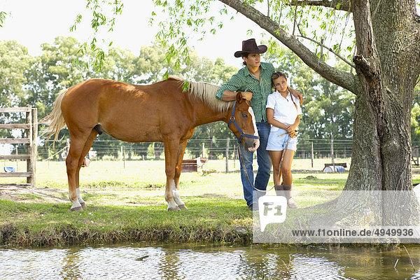 Paar ständigen mit einem Pferd in der Nähe von einen Teich