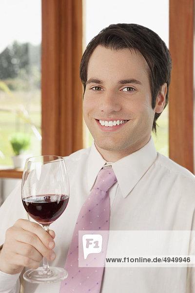 Unternehmer hält Rotwein in der Küche