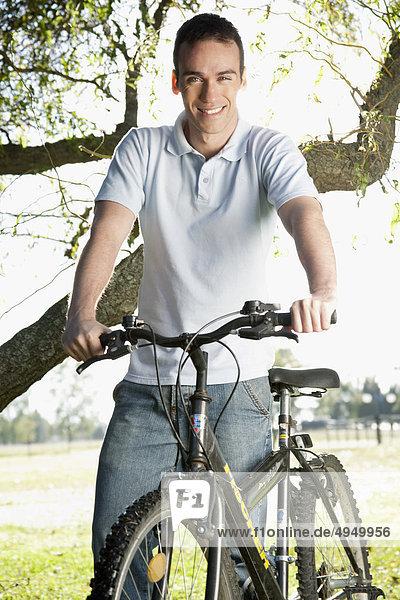 Mann mit einem Fahrrad in einem park