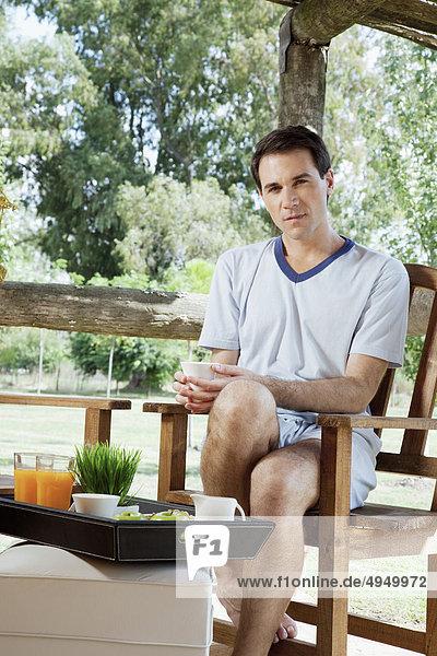 sitzend Mann Stuhl trinken Tee