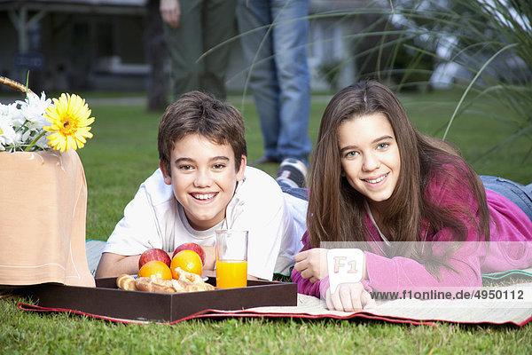 Kinder mit einem Picknick mit ihrer übergeordneten hinter Ihnen