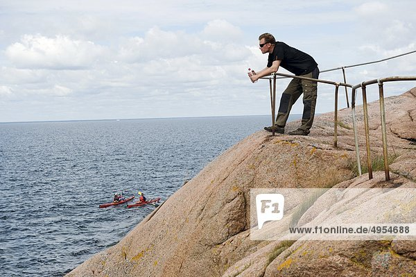 Man standing on cliff  side view