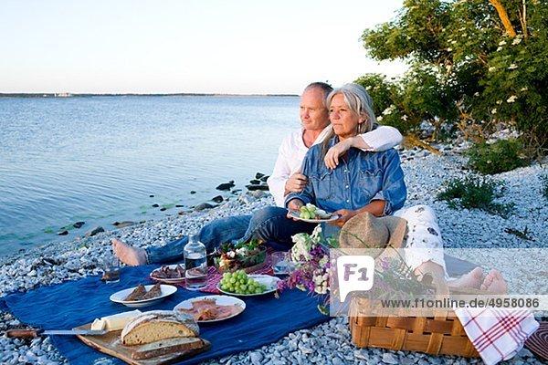 reifes Paar mit Picknick am Strand