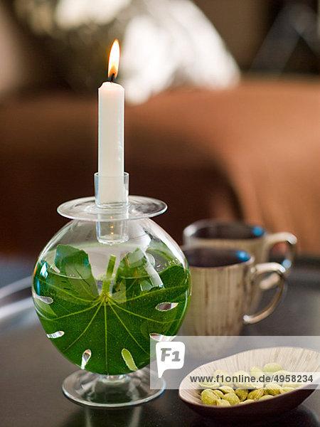 Kerze auf Tisch mit Cups und Nüssen