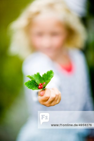 Mädchen hält rote Johannisbeeren mit Blatt  Nahaufnahme