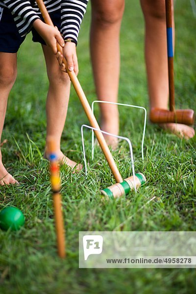 Children playing croquet  low section
