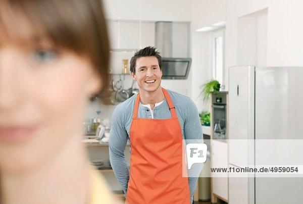 Mann und Frau stehen in der heimischen Küche