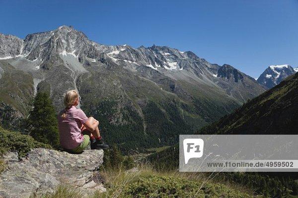 Schweiz  Wallis  Reife Frau sitzend und mit Blick auf den Mont Collon
