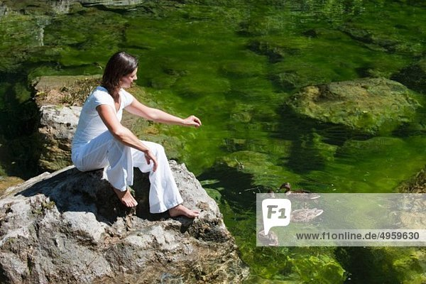 Österreich  Salzburg  Mittlere erwachsene Frau auf einem Stein sitzend und Vögel fütternd