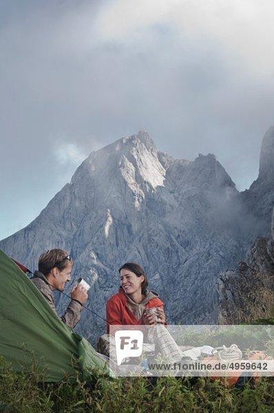 Österreich  Salzburg  Filzmoos  Paar sitzend neben Zelt am Berg