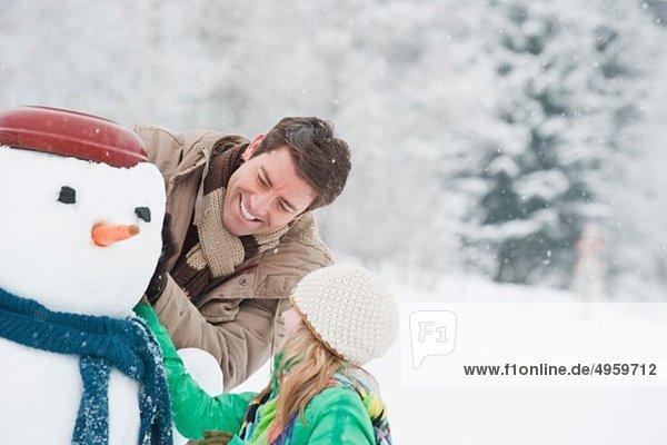 Austria  Salzburg  Hüttau  Father and daughter with snowman  smiling