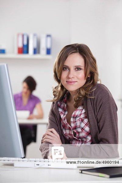Junge Frau lächelt mit Geschäftsfrau im Hintergrund