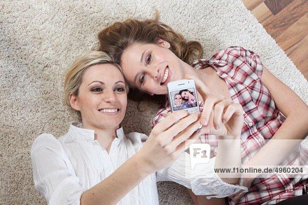 Deutschland  Bayern  München  Junge Freunde fotografieren sich selbst mit dem Handy  lächelnd