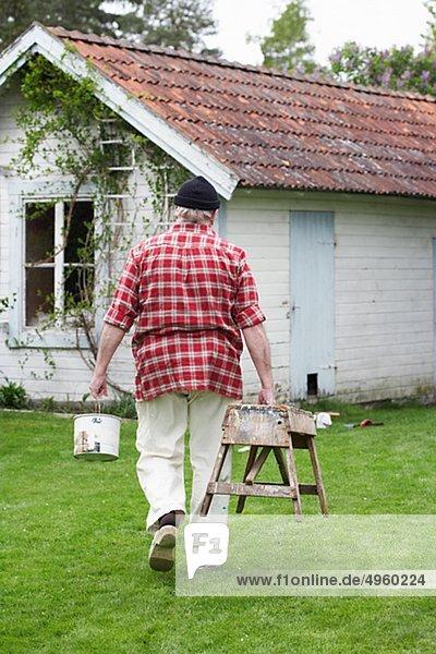 Elderly man painting his summer cottage  Sweden.