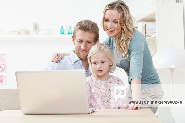 Deutschland  Bayern  München  Familie mit Laptop  lächelnd