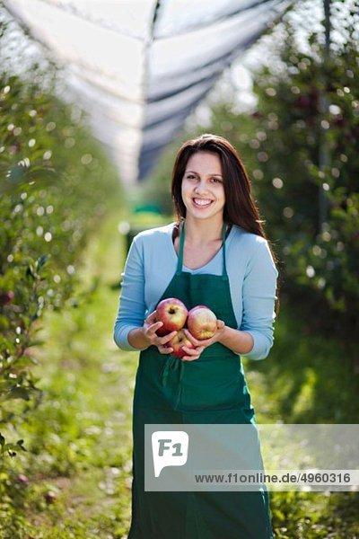 Kroatien  Baranja  Junge Frau mit Äpfeln  lächelnd  Portrait