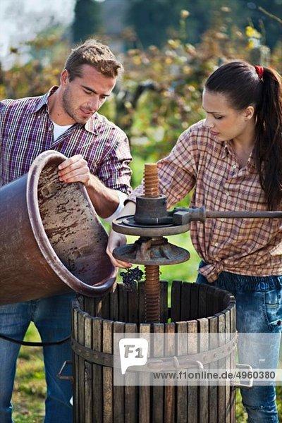 Kroatien  Baranja  Junger Mann und Frau neben Weinpresse