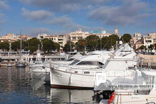 Spain  Balearic Islands  Majorca  Porto Cristo  View of moored boat with buildings in background