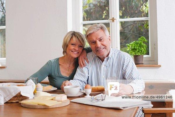 Deutschland  Kratzeburg  Seniorenpaar beim Frühstück  lächelnd  Portrait