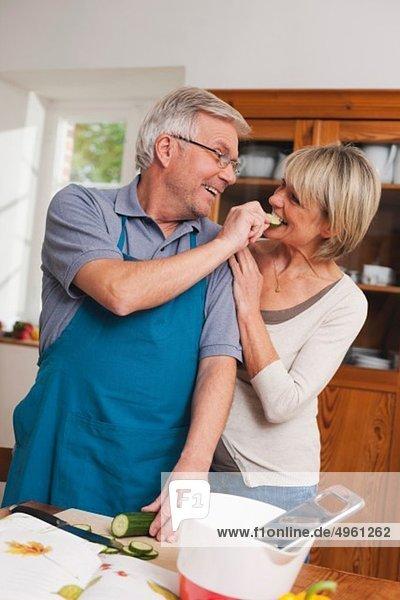 Senior Mann füttert Gurkenscheibe an Seniorin
