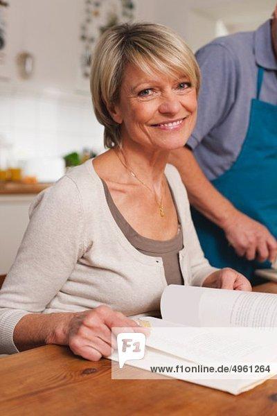 Deutschland  Kratzeburg  Seniorenpaar bei der Zubereitung von Speisen aus dem Kochbuch