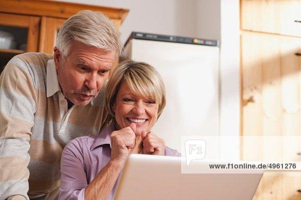 Deutschland  Kratzeburg  Senior Paar mit Laptop  lächelnd