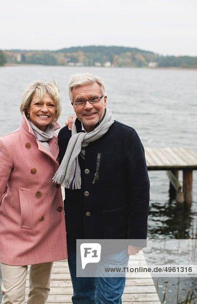 Deutschland  Kratzeburg  Seniorenpaar auf Promenade stehend  lächelnd  Portrait