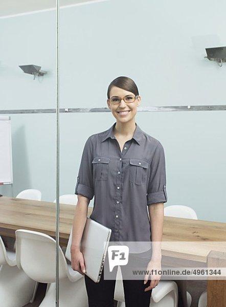 Junge Frau mit Laptop im Büro  lächelnd  Portrait