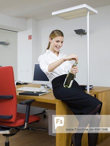 Junge Frau genießt Sekt im Büro