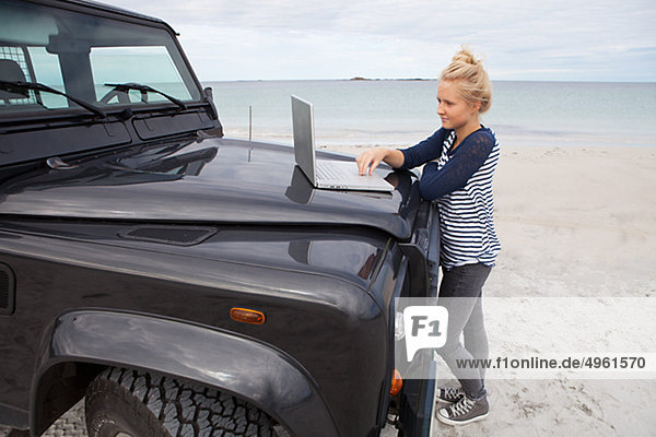 Teenage girl standing by off road vehicle and using laptop  side view
