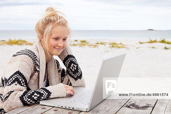 Teenage girl sitting at table  using laptop