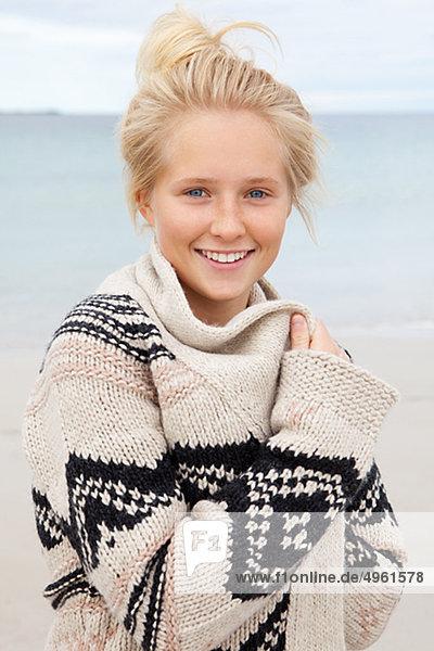Teenage girl standing on beach  portrait  smiling