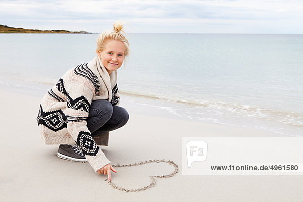 Teenage girl making heart shape on sand  smiling  portrait