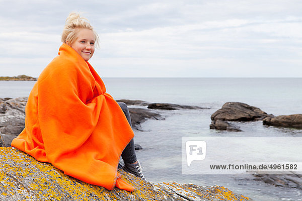 Teenage girl wrapped in blanket sitting by sea  smiling