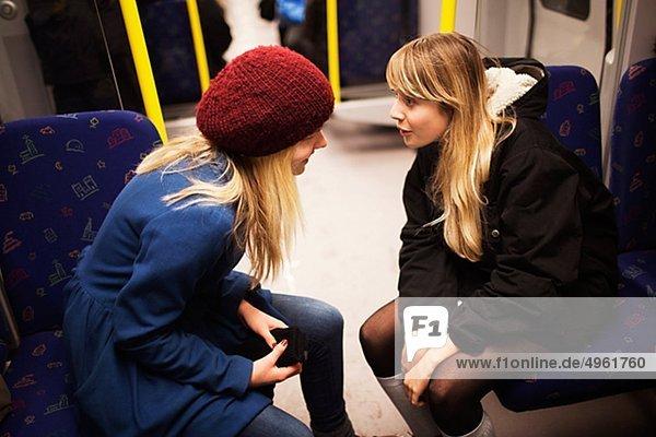Jugendlicher sprechen 2 Mädchen U-Bahn Zug