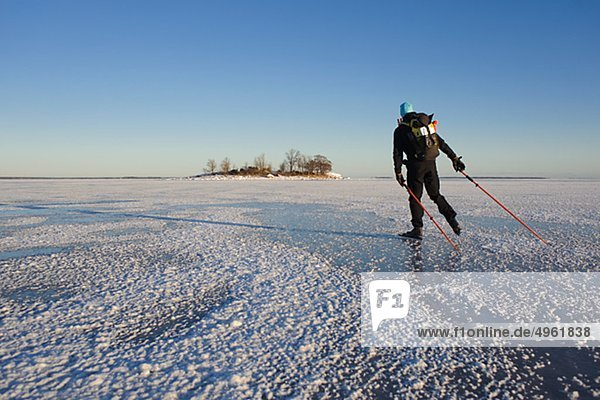 Mann Eislaufen auf Schnee bedeckt Landschaft