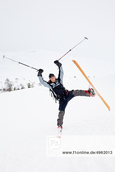 Man with ski and ski pole messing about in snow nat90234