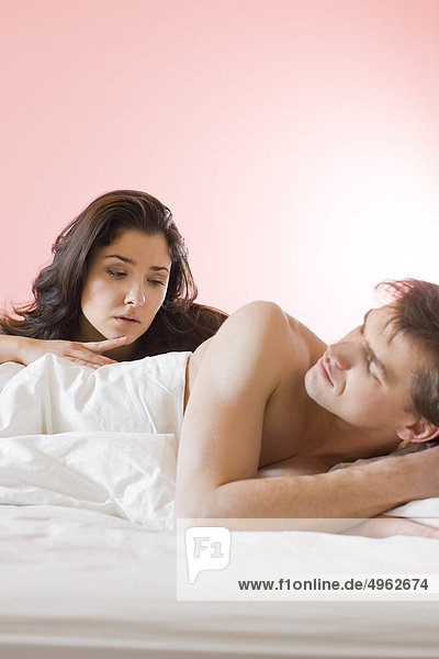 Sad woman talking with man in bed