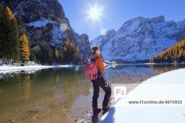 Frau steht am Pragser Wildsee im Winter  Südtirol  Italien