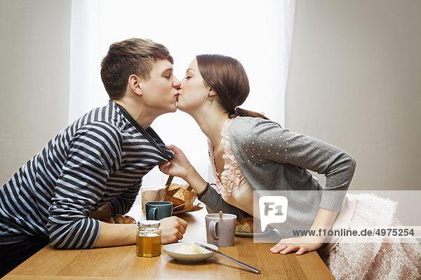 Frau küsst Freund über Tisch