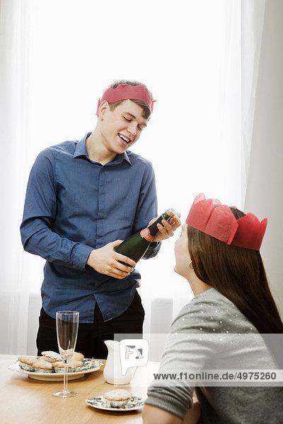 Mann öffnet Flasche Champagner
