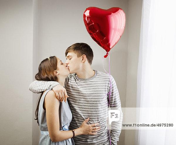 Ein Paar küsst sich  hält einen Herzballon.